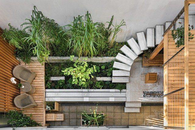 der Innenhof eines tiny houses aus Holz, einer Treppe aus Stahlbeton und hohen Pflanzen