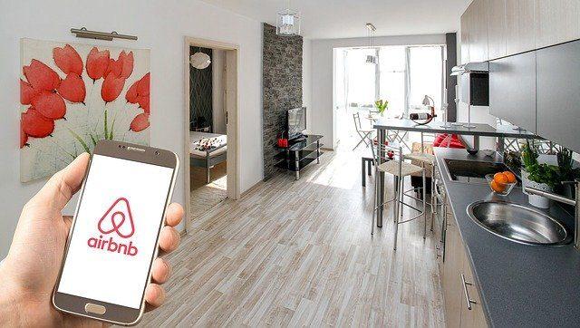 ein Wohnesszimmer im Hintergrund und vorne links im Bild eine Hand mit einem Handy auf dem die Seite Airbnb zu sehen ist