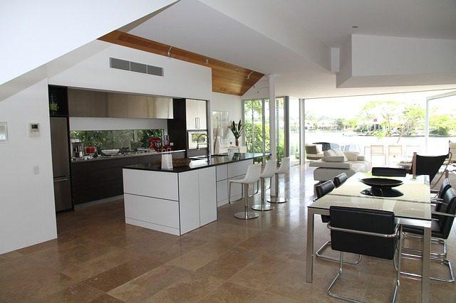 links eine amerikanische Küche, gegenüber ein großer Glastisch mit schwarzen Stühlen und im hinteren Bereich das Wohnzimmer mit offener Wand zum Garten
