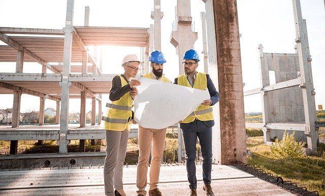 drei Architekten die auf einer Baustelle auf einen plan sehen, alle haben einen Helm auf und eine gelbe Weste an