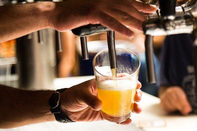 zwei Hände einer Person die gerade ein Bier zapfen