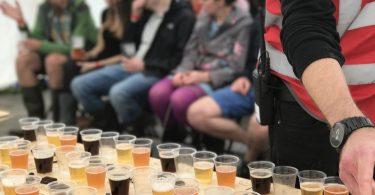 Bierdegustation auf dem Bierfestival, mehrere Leue sitzen in Stuhlreihen vor einem Tisch mit kleinen bechern die mit verschiedenen Biersorten gefüllt sind