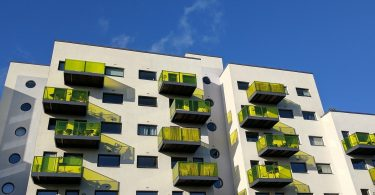 ein sechsstöckiges Wohngebäude mit gelben Balkonen