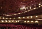 ein leeres Theater von innen, zu sehen sind die samtroten sitze und die verzierte Decke mit Lichtern