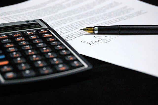 ein schwarzer Tisch auf dem ein Taschenrechner, ein Vertrag und auf dem Vertrag ein Füllfederhalter liegt