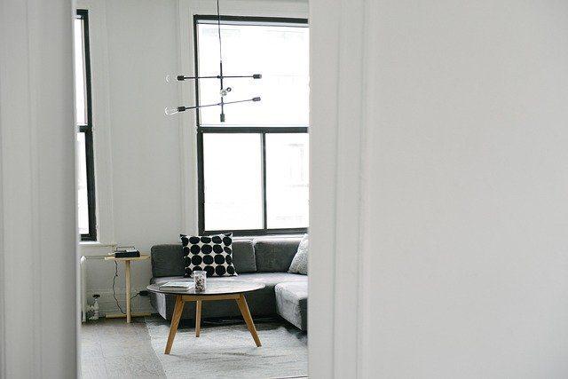die offenen Tür einer Wohnung durch die man ein Wohnzimmer mit einem grauen Sofa und einen kleinen Holztisch sieht