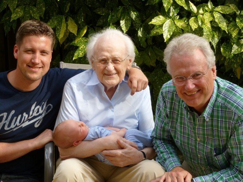 vier generationen die in die Kamera lächeln, baby, Vater, opa und Uropa