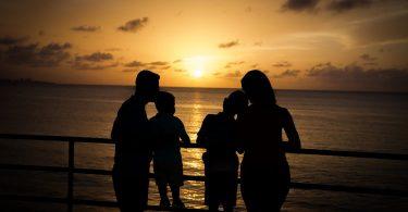 ein Mann und eine Frau in deren Mitte zwei kleine Kinder die auf einem Gelände stehen und sich jeweils mit dem Kopf an einen Erwachsenen lehnen während sie einen Sonnenuntergang beobachten