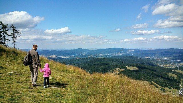 ein mann mit einem kleinen Kind die sich die Hände halten und von einem Berg ins Tal sehen