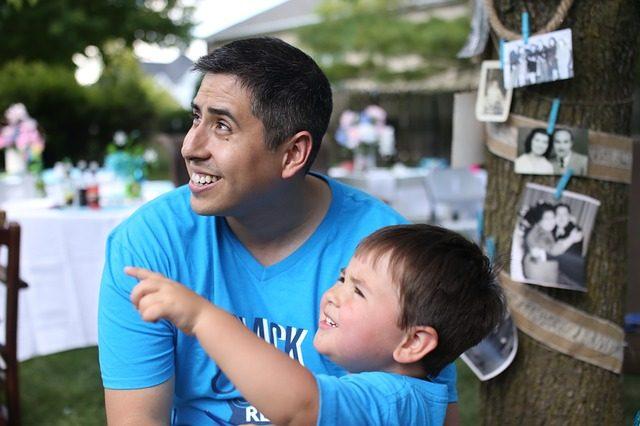 Vater und Sohn im blauen T-Shirt der vater lächelt und schaut in die Richtung in die der junge mit dem Finger zeigt