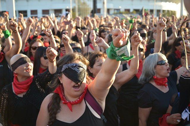 Frauenstreik, alle Frauen halten ihre linke Faust in die Luft, viele haben sich ihre augen mit einem schwarzen Tuch oder einer Sonnenbrille verdeckt und alle sind schwarz gekleidet