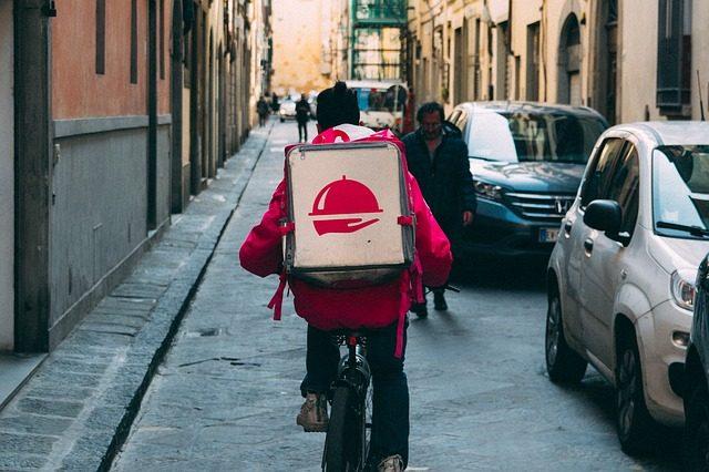 eine Person auf einem Fahrrad die durch die Straße fährt und hinten einen Rucksack mit essen trägt