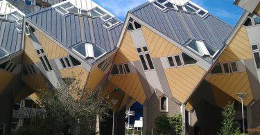 gelb-graue würfelförmige Häuser die aneinander zwischen anderen Häusern hängen