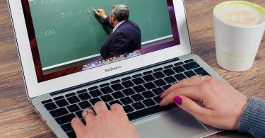 eine Person die an einem Laptop etwas schreibt während sie ein video von einem Lehrer sieht der eine mathematische Operation erklärt