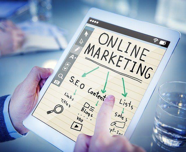 eine Person die eine Tablet in der linken Hand hält und mir der rechten hand ein online marketing System erklärt das auf dem Bildschirm zu sehen ist