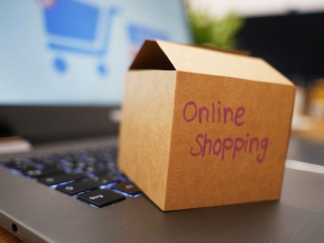 ein offener eingeschalteter Laptop mit einer kleinen Kartonkiste auf der Tastatur auf der mit lilanem Stift online shopping geschrieben steht