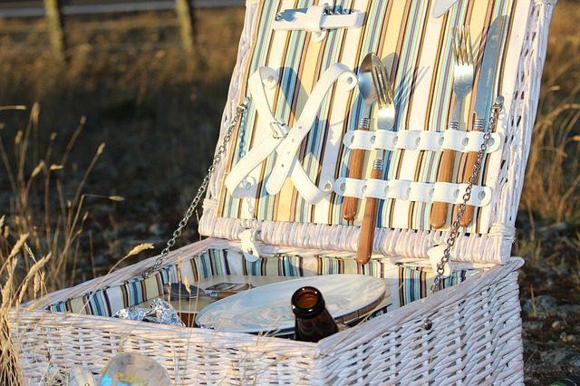 eine weißer viereckiger offener Picknickkorb mit Besteck und kleinen Tellern darin