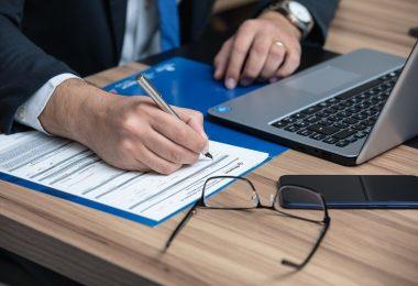 die arme eines Mannes im Anzug mit weißem Hemd und blauer Krawatte wie er gerade einen vertrag ausfüllt, vor ihm liegen eine Brille, ein Handy und ein Laptop auf einem Holztisch
