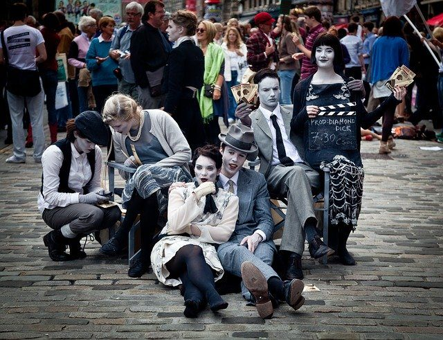 eine Gruppe von Schauspielern die in einer Fußgängerzone Werbung für ihre Aufführung machen