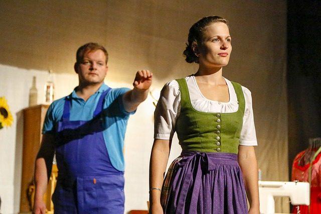 zwei Schauspieler die auf der Theaterbühne ein Eheleben darstellen, vorne eine Frau im Kleid und dahinter ein mann im blauen Arbeitsanzug der den Arm nach ihr ausstreckt