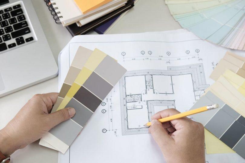 zwei Hände, die rechte notiert etwas in einen Bauplan und die Linke hält verschiedenen Farbbeispiele