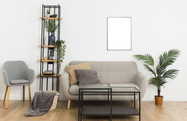 ein minimaoistisches Wohnzimmer mit einem kleinen grauen Sofa, einem schwarzen Metalltisch und einem schmalen hohen Regal