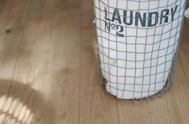 ein weißer Wäschekorb auf dem in blauen Buchstaben Laundry N. 2 steht auf einem Parketboden