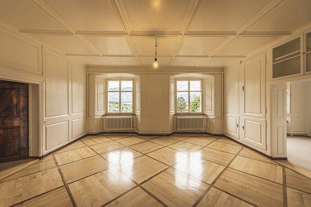 das Wohnzimmer einer unmöblierten Wohnung mit zwei großen Fenstern und links einem Kamin