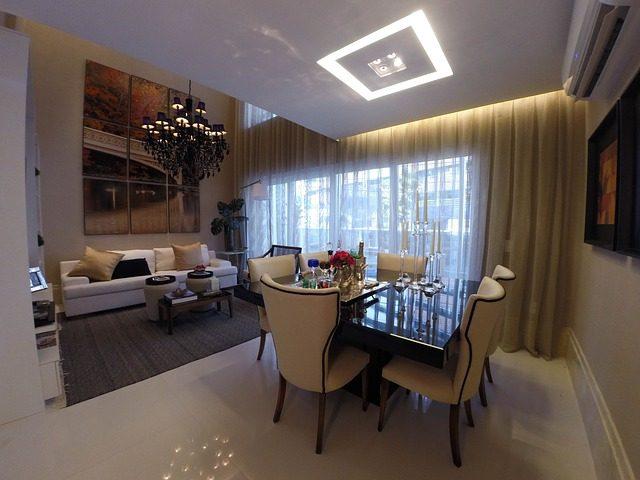 ein prunkvolles Ess/Wohnzimmer mit weißen Möbeln und einem großen schwarzem Kronleuchter an der Decke