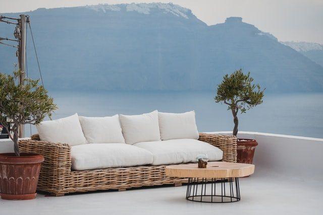 eine Terrasse mit einem kleinen Holztisch und einem Viersitzer Sofa mit weißen Kissen