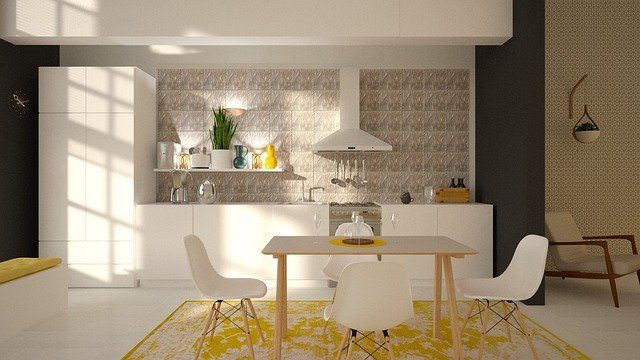 Esstisch auf einem gelben Teppich und dahinter eine weiße Küche