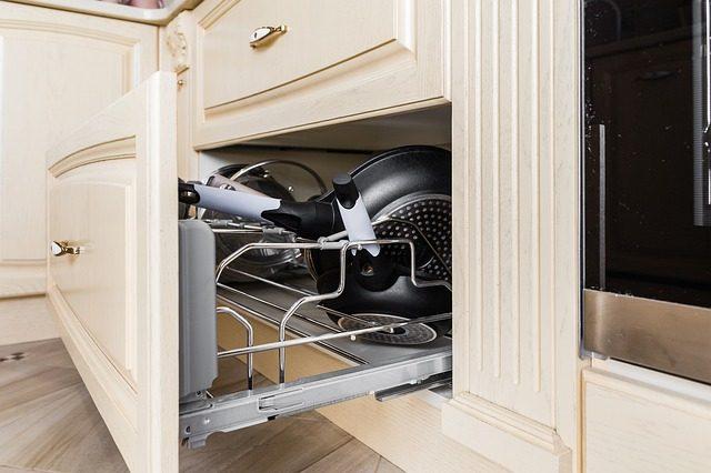 eine halboffenen Küchenschublade mit Pfannen