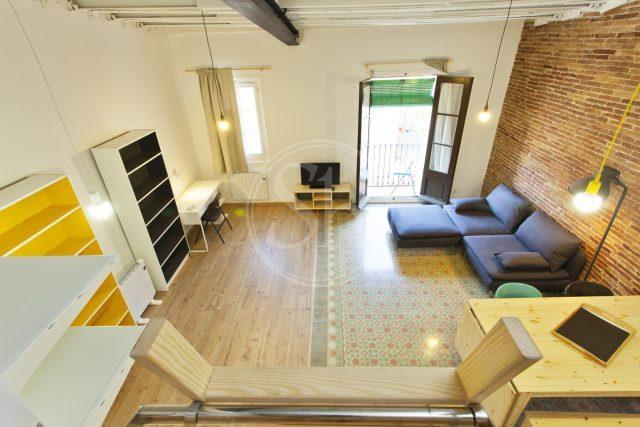 Loft zur Miete in Polble Sec, zu sehen ist ein Zimmer mit blauem Sofa, ein weißer Schreibtisch mit Stuhl und einige Regale an der Wand daneben