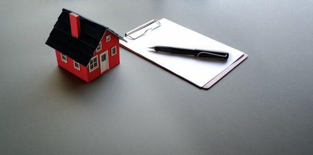 ein kleines rotes Spielzeughaus das neben einem Notizblock und einem schwarzem Kugelschreiber auf einem grauem Tisch steht