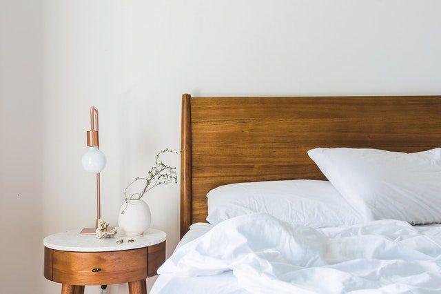 ein Holzbett mit weißer Bettwäsche und links daneben ein Holznadchtkästchen mit einer minimaoistischen Stehlampe und einer weißen eiförmigen Vase mit einem kleinem Ast darin