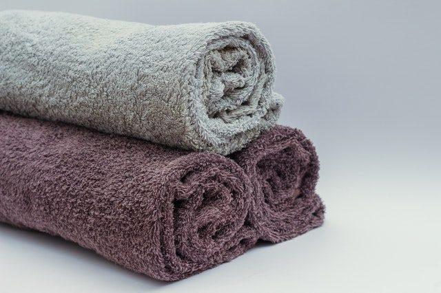 zwei eingerollte braune Handtücher und mittig darauf ein graues eingerolltes Handtuch
