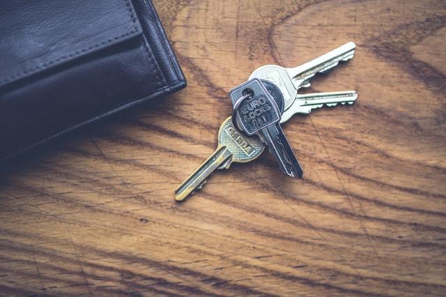 eine Holzfläche auf der ein Schlüsselbund und ein schwarzer Geldbeutel liegt