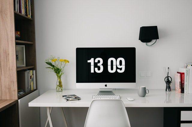 ein Büro mit einem weißen Schreibtisch und Stuhl, ein großer Computerbildschirm auf dem die Uhrzeit 13:09 zu sehen ist und eine weiße Tastatur davor