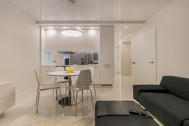 foto eines Apartments, vorne rechts ein dunkelgraues Sofa un ein schwarzer Tisch, mittig im Raum ein kleiner weißer Esstisch mit vier Stühlen und ganz hinten eine weiße Küchenzeile