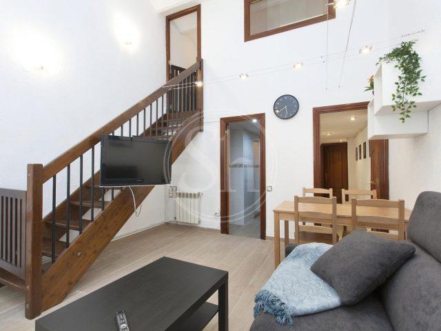 Studentenwohnung in Sants, graues Sofa, ein schwarzer Tisch und gegenüber eine Holztreppe an der ein Fernseher befestigt ist