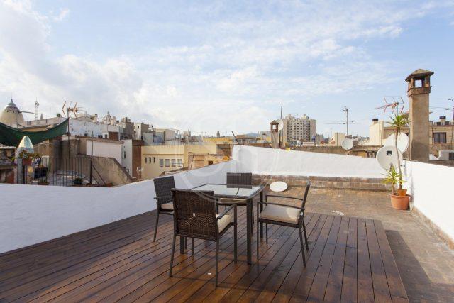 Wohnung in Ciutat Vella, zu sehen ist die Dachterrazze mit Holzboden, ein viereckiger Tisch und vier schwarze Stühle