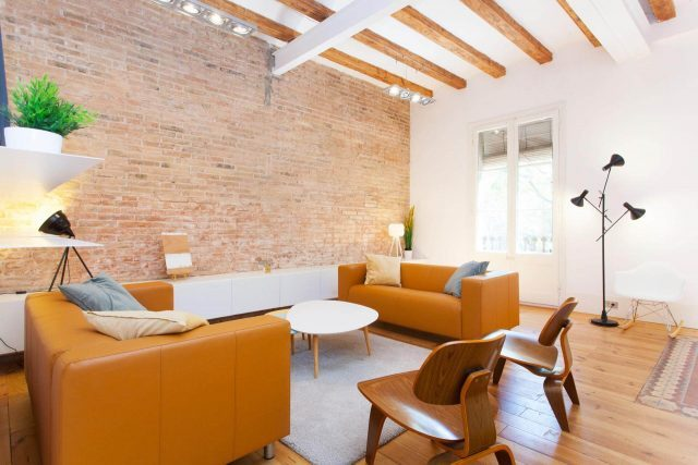 Wohnung zu vermieten in Graicia, zu sehnest das Wohnzimmer in orangenen und grauen Tönen