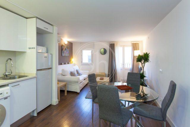 Wohnung an der Rambla, zu sehen ist ein Apartment mit Küche vorne links, rechts der Esstisch und dahinter ein weißes Sofa