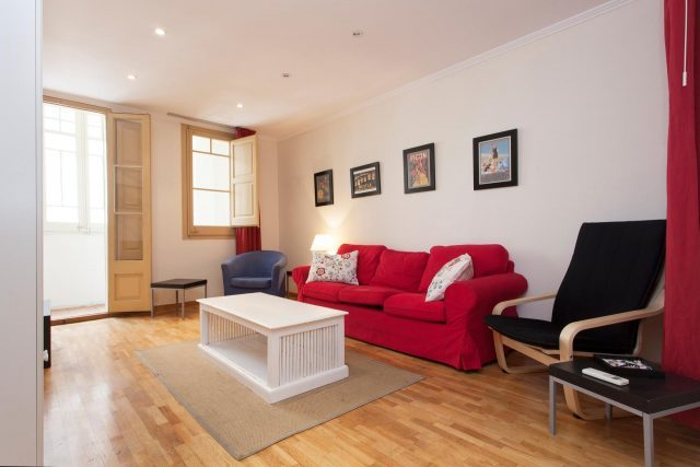 Wohnung in Les Corts, zu sehen ist das Wohnzimmer mit einem rotem Sofa und einem weißen Tisch davor