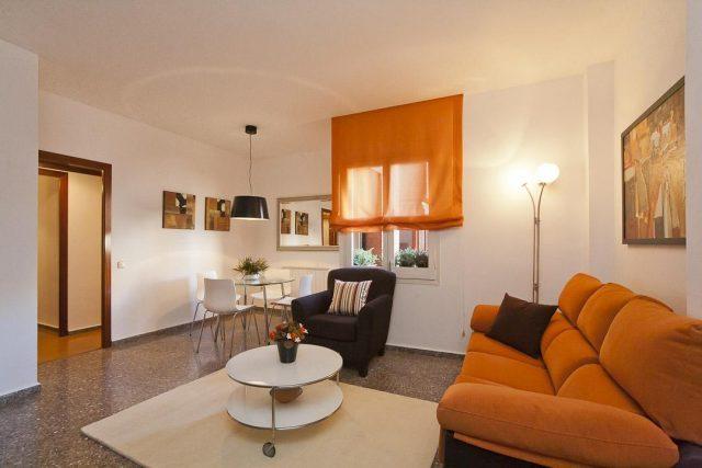 Wohnung zu vermieten in Marina, zu sehen ist das Wohnzimmer mit einem kleinem weißen Tisch, ein schwarzer Sessel ein orangenes Sofa und ein weißer Esstisch mit vier Stühlen