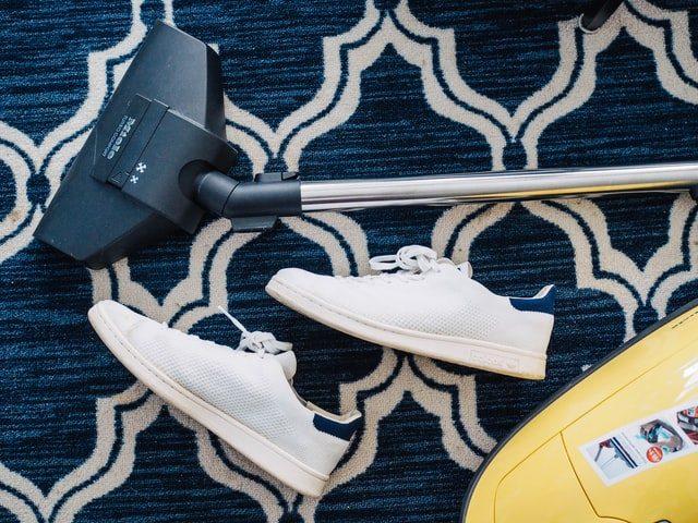 ein blau gemusterter Teppich auf dem weiße Turnschuhe und ein gelber Staubsauger liegen