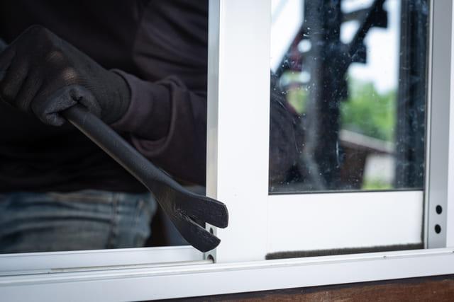 eine dunkel gekleidete Person die mit Hilfe eines Eisenstabs ein Fenster auf macht