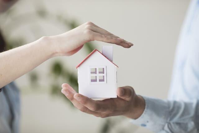 die Hand eines Mannes in der ein kleines weißes Haus mit rotem Dach steht und die Hand einer Frau darüber