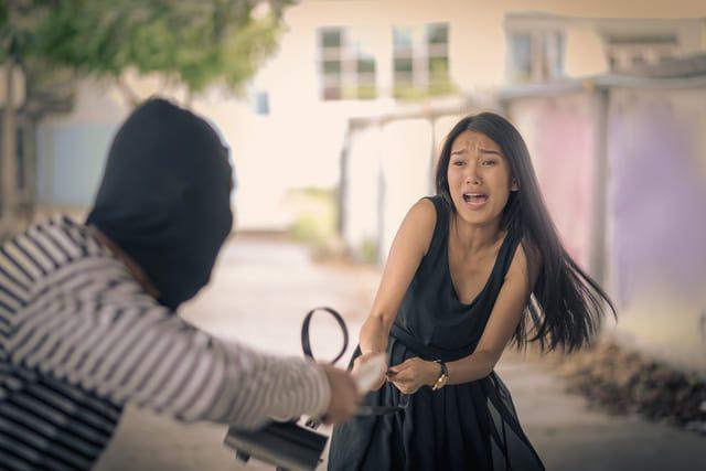 eine Person mit verdecktem Gesicht die einer jungen Frau die Handtasche aus der Hand reist