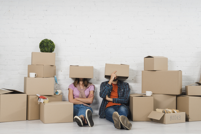 ein Mann und eine Frau die zwischen Umzugskartongs auf dem Boden sitzen wobe jeder einen Karton auf dem Kopf hat